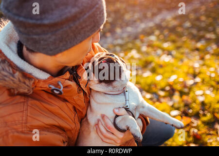 Master holding pug dog in hands in autumn park. Happy puppy looking on man and showing tongue. - Stock Photo
