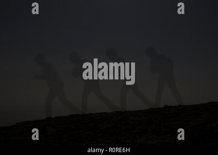 at dusk, many shades of the man on the slope against the sky, a man goes and leaves a shadow. the shadows multiplied. in the background stars. in the foreground of the trail and hillside - Stock Photo