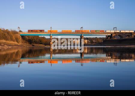 DB cargo class 66 locomotive crossing  Carlisle Bridge (Lancaster, river Lune) with the 1407 Liverpool Seaforth - Mossend  intermodal container train - Stock Photo