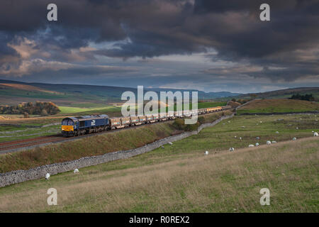 Direct rail Services class 66 locomotive passing Selside on the settle -Carlisle line with a freight train carrying railway ballast for Network Rail - Stock Photo
