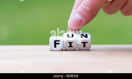 Hand is turning a dice and changes the word 'fit' to 'fun' - Stock Photo
