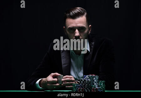 A wealthy man playing poker with the excitement in a casino. - Stock Photo