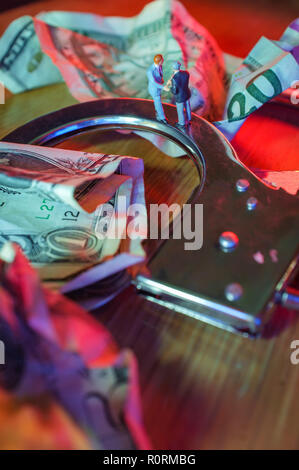 Conceptual miniature criminal businessmen shake hands standing on top of handcuffs with crumpled dollar bills and police lights - Stock Photo