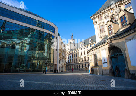 Pedestrains walk along the street in front of the University of Wroclaw, main building.  Magnificent Baroque facade  with clear blue sky background - Stock Photo