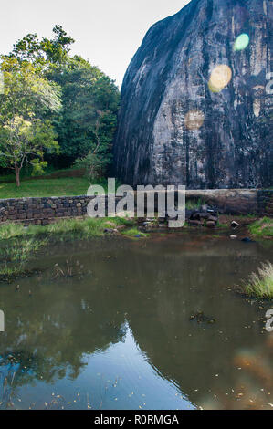 Sigiriya Rock (Lion Rock), near Dambulla, Sri Lanka. Large granite rock and one of the many bathing pools in the Royal Gardens. - Stock Photo