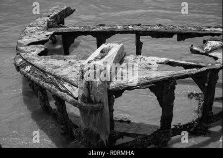 Old shipwreck, Galle Fort, Sri Lanka, Black and white image, rusted remains of fishing vessel on shoreline. - Stock Photo