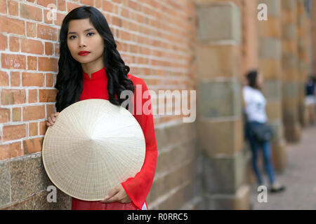 Attractive young Vietnamese woman wearing traditional clothing holding her hat in front of her as she leans against a brick building in an urban stree - Stock Photo