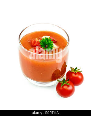 Tomato soup gazpacho in a glass with parsley and vegetables isolated on white background - Stock Photo