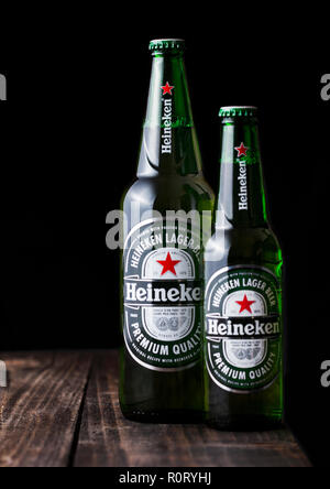 LONDON, UK - APRIL 27, 2018: Bottles of Heineken Lager Beer on dark wooden background. Heineken is the flagship product of Heineken International - Stock Photo