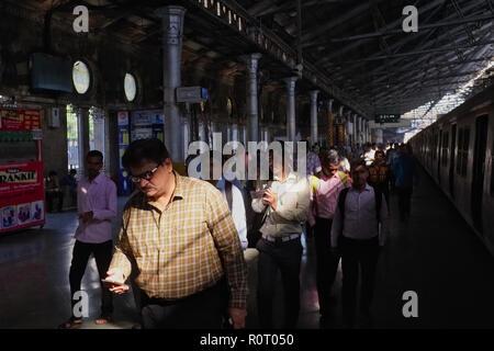 A passenger disembarked from a commuter train at Chhatrapati Shivaji Maharaj Terminus (CSMT), Mumbai, India, checking on his mobile phone
