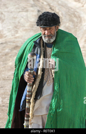 Old Sufi Man Wearing Green Coat Walking In The Desert With Stick Towards Hashish Smoking Den, Old Balkh, North Afghanistan - Stock Photo