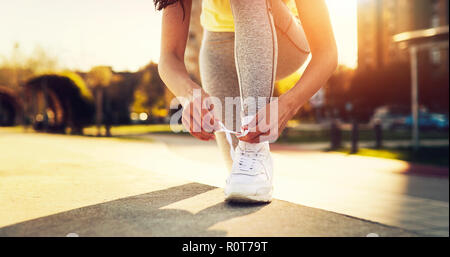 Attractive sportswoman tying shoelace and getting ready for fitness - Stock Photo