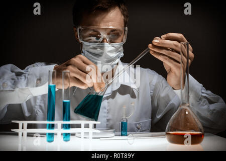 Young man scientist using auto-pipette with flask in medical science laboratory. Researcher concept. - Stock Photo