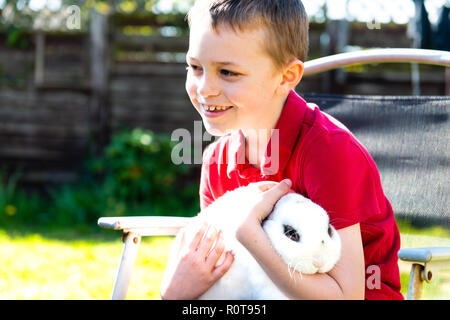 A handsome happy smiling little boy with autism, Aspergers syndrome and adhd cuddling his favourite pet rabbit in the garden at home - Stock Photo