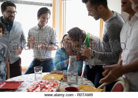 Affectionate Latinx family celebrating grandmothers birthday - Stock Photo
