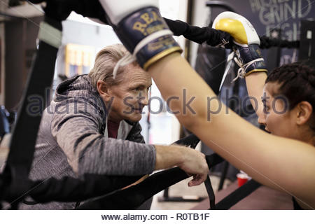 Trainer talking with female boxer in gym - Stock Photo