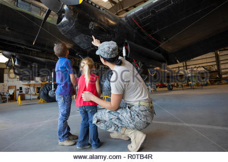 Female army engineer mother showing airplane to children in airplane hangar - Stock Photo