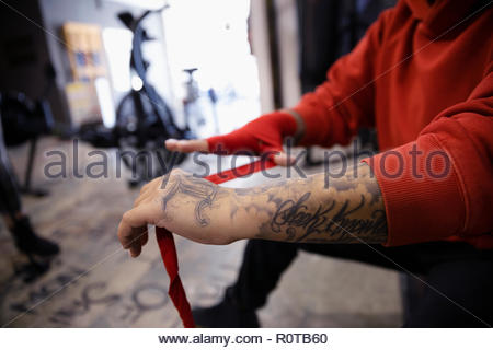 Close up tough female boxer with tattoos wrapping wrists in gym - Stock Photo