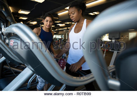Female personal trainer guiding woman using treadmill in gym - Stock Photo