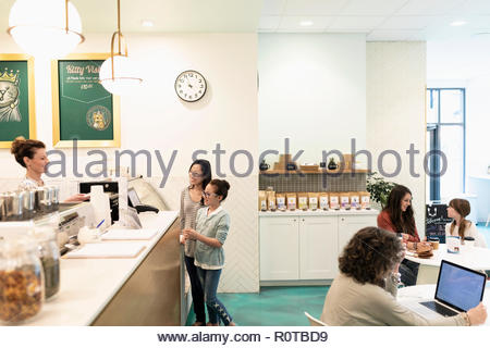 Mother and daughter order at cafe counter - Stock Photo