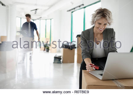Businesswoman with credit card paying bills at laptop in new office with cardboard boxes - Stock Photo