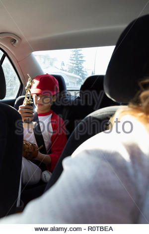Boy in baseball uniform holding trophy in back seat of car - Stock Photo