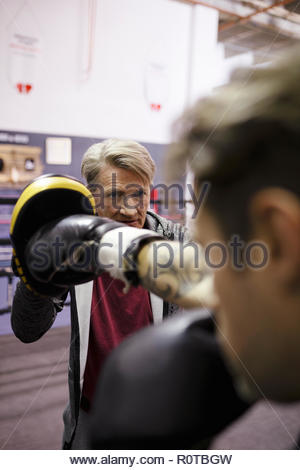 Trainer and male boxer training in gym - Stock Photo