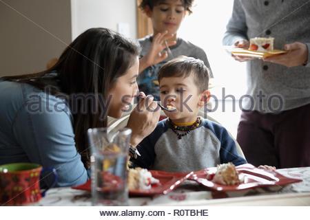 Latinx mother feeding birthday cake to toddler son - Stock Photo