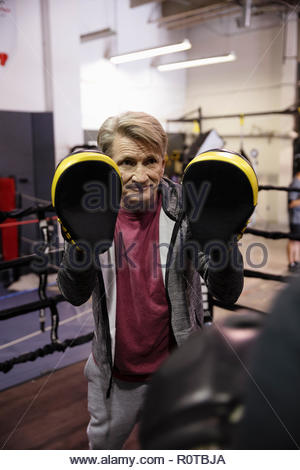 Male trainer with boxing pads in gym - Stock Photo