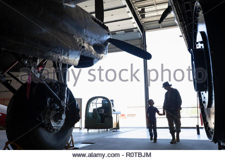 Female army engineer mother walking with son in military airplane hangar - Stock Photo