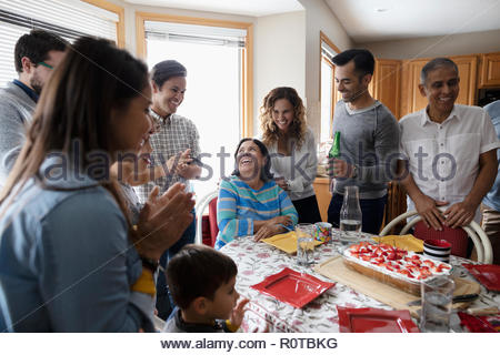 Latinx multi-generation family celebrating birthday with cake at kitchen table - Stock Photo