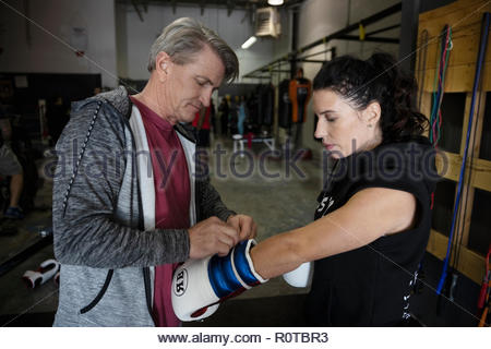 Trainer helping female boxer putting on boxing gloves in gym - Stock Photo