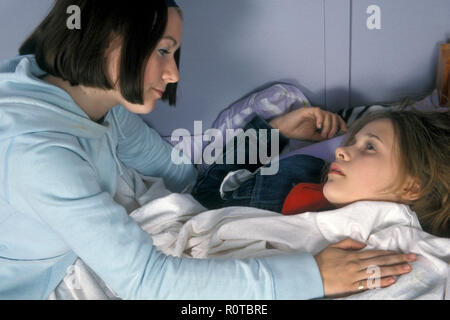 teenage girl consoling her friend who is lying on the bed with a hangover or high on substance abuse - Stock Photo
