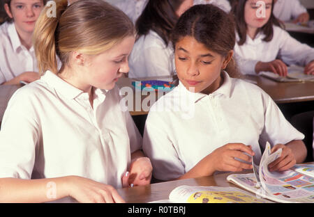 two high school girls in classroom - Stock Photo