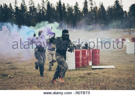 Paintballing team with smoke bombs running in field - Stock Photo