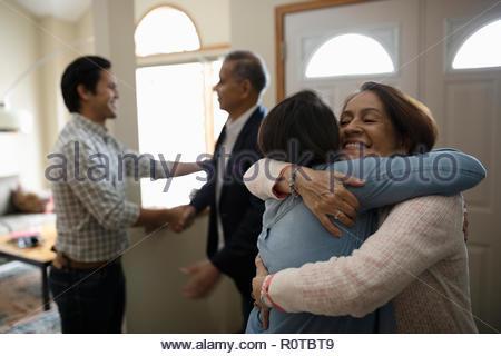 Latinx couple greeting parents - Stock Photo