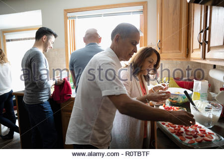 Latinx senior couple decorating cake with strawberries in kitchen - Stock Photo