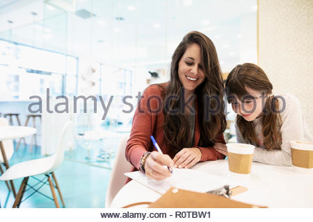 Smiling mother and daughter drinking coffee and filling out adoption application in cat cafe - Stock Photo
