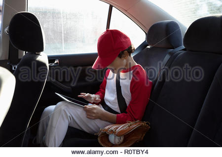 Boy in baseball uniform using digital tablet in back seat of car - Stock Photo