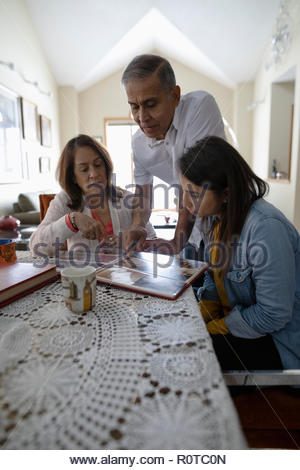 Latinx family looking at photo album - Stock Photo