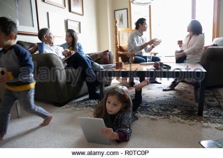 Latinx multi-generation family talking and relaxing in living room - Stock Photo