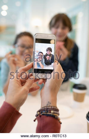 Woman with camera phone photographing girls - Stock Photo