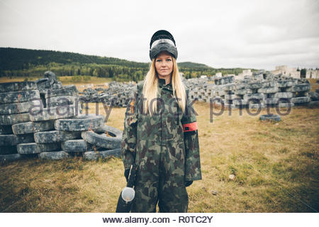 Portrait confident young woman paintballing in field with tires - Stock Photo