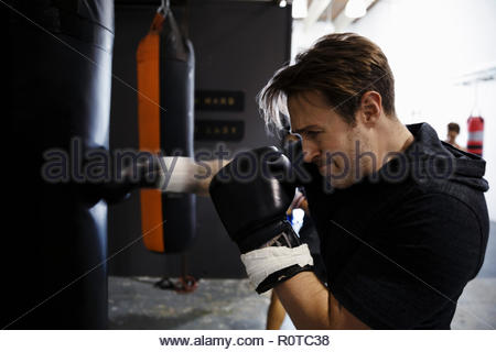 Tough male boxer training, boxing at punching bag in gym - Stock Photo