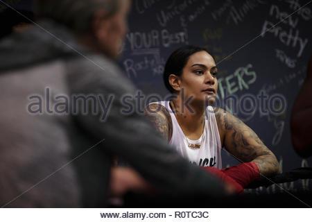Tough female boxer resting in gym - Stock Photo