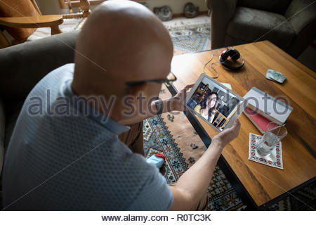 Latinx man video chatting with woman on digital tablet - Stock Photo