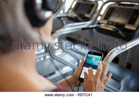 Woman checking fitness tracker on smart phone at treadmill in gym - Stock Photo