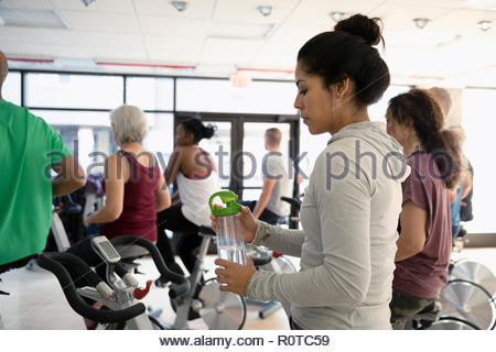 Woman with water bottle preparing for spin class in gym - Stock Photo