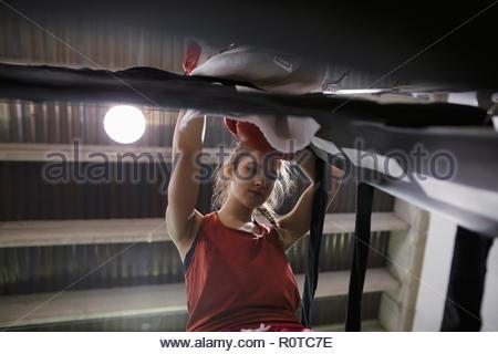 Tough female boxer resting in boxing ring corner - Stock Photo