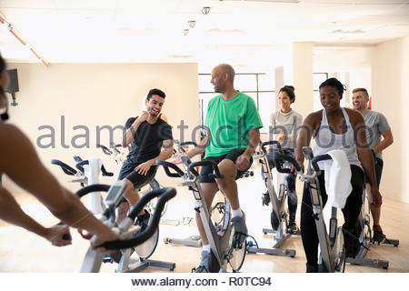 Men high-fiving on exercise bikes in spin class in gym - Stock Photo